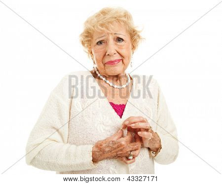 Senior woman with arthritis is having trouble buttoning her sweater. Isolated on white.