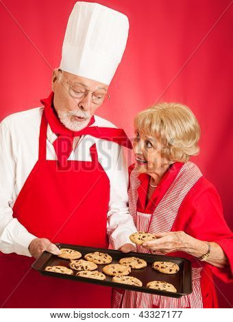Professional baker shares a tray of fresh chocolate chip cookies with a sweet senior housewife.