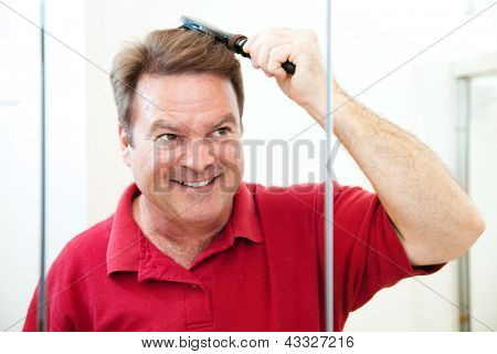 Handsome middle-aged man brushing his hair, looking in the bathroom mirror.