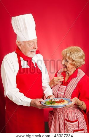 Chef teaching a sweet elderly grandma how to cook authentic Italian spaghetti marinara.  Red background with copy space.