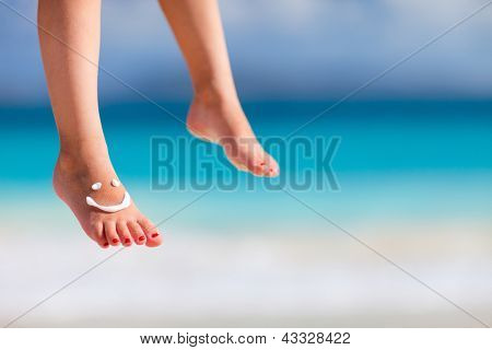 Close up of child feet with smile made with sun cream