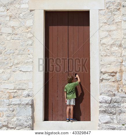 Young Boy In Front Of A Big Door