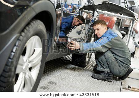 auto trabajador reparador en automoción, examinando la pintura del cuerpo del coche o pintar en auto reparación s