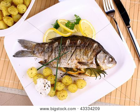 Grilled Fish Served With Potatoes, Lemon And Sauce