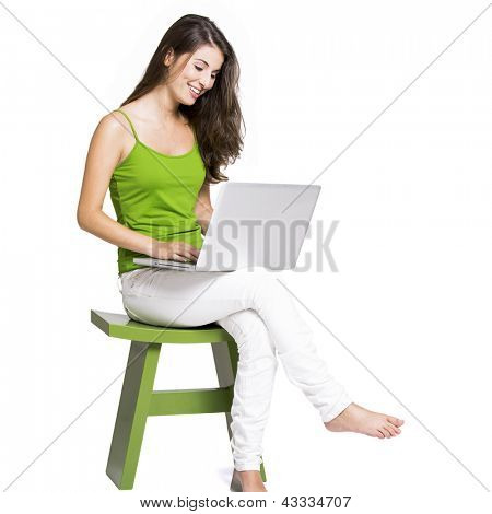 Beautiful woman sitting in a chair working with a laptop, isolated over a white