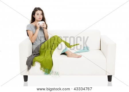 Beautiful woman on a sofa drinking tea, isolated over a white background