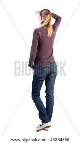 Rückansicht des stehende junge Frau. Mädchen deckt seine Augen vor grellem Licht. Mädchen in Jeans zu sehen