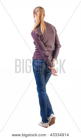 back view of standing young beautiful  blonde woman. girl in jeans and sweater watching.shy girl waits. Rear view people collection.  backside view of person.  Isolated over white background.