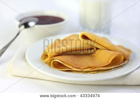 Crepes With Confiture And Milk On Background