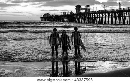 Three surfing friends near the Oceanside Pier, Oceanside, California. Black and white.