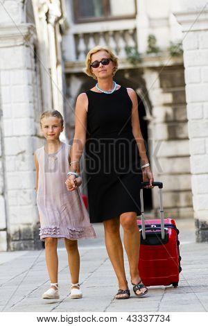 Touring Venice - lovely girl and mother with the suitcase in Venice  (travel to famous places in Europe, concept)