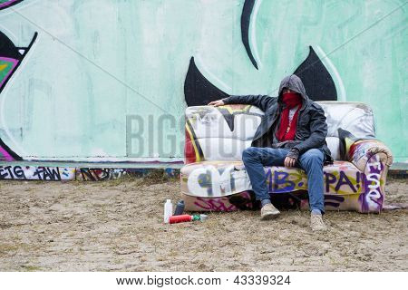 Graffiti Artist posing on a spray painted, old, couch in front of a large concrete wall with artwork on it