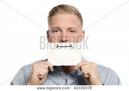 Serious young businessman holding empty white card with space for text in front of his mouth isolated on white background.