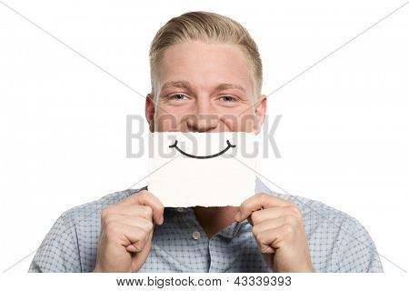 Smiling young businessman holding blank white card with space for text in front of his mouth isolated on white background.