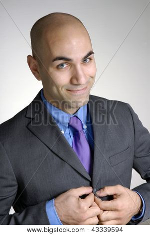 successful bald head young businessman portrait,buttoning his jacket.