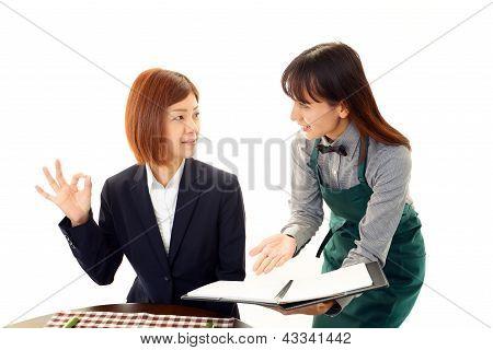 Waitress shows the menu to customer