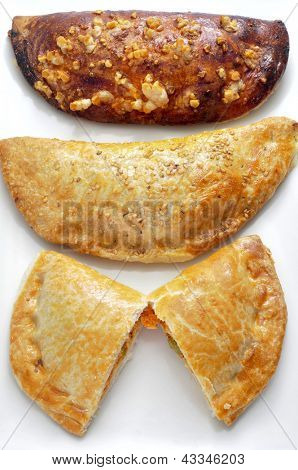 closeup of some different empanadas, cakes stuffed with vegetables and or meat or tuna, on a white background