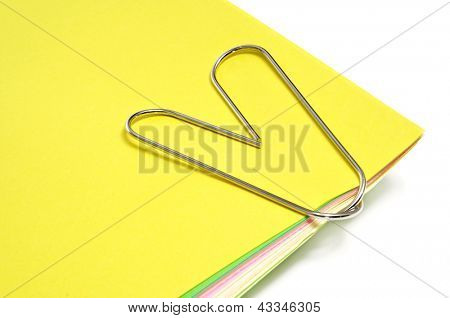 a heart-shaped paperclip fastening sheets of paper of different colors on a white background