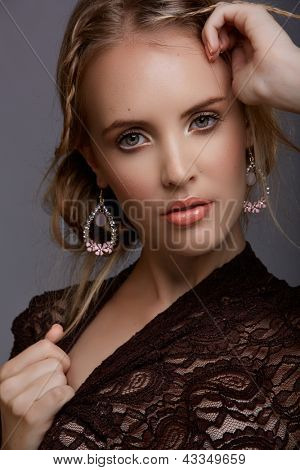 Portrait of a sensual woman model with messy braided hair on wearing fashion lace top and luxury chandelier earrings. Hi-end retouched to preserve natural complexion with some freckles