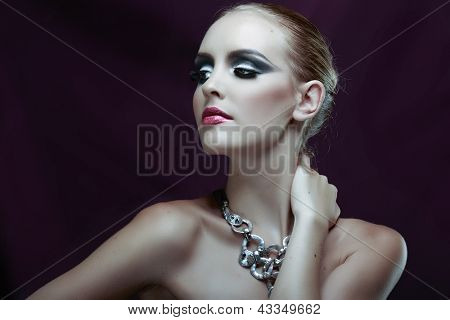 Portrait of a beautiful model in a dark evening fashion make-up on purple background wearing statement silver necklace