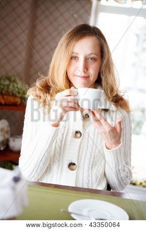 Smiling Young Woman With A Cup Of Coffee In Hand