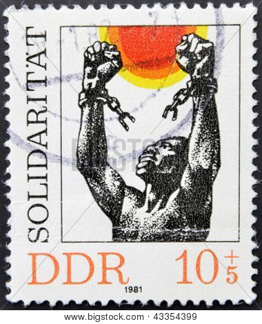 stamp printed in Germany shows a black man breaking the chains of slavery