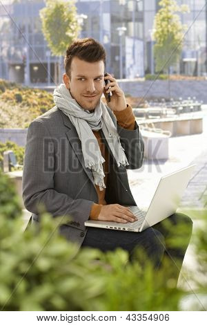 Young businessman sitting in citypark, talking on mobilephone, using laptop computer.