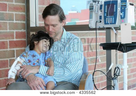 Worried Father Holding Child In Hospital