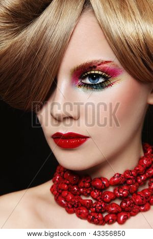 Portrait of young beautiful woman with bright fancy make-up and hairstyle