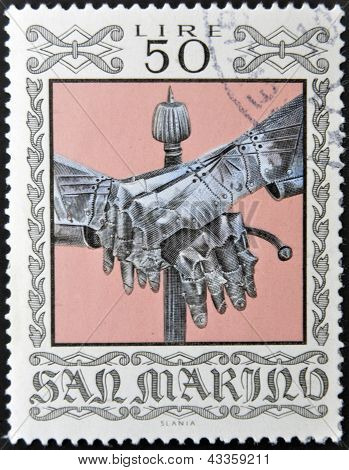 stamp printed in San Marino dedicated to Ancient Weapons from Cesta Museum shows Gauntlets and Sword
