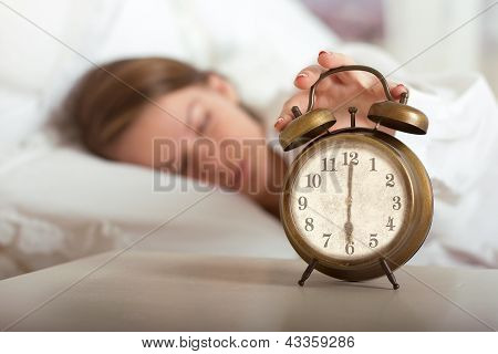 Woman's hand off the alarm clock 6 am