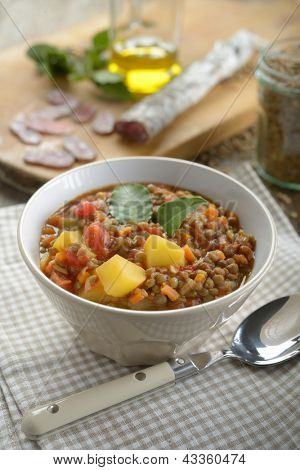 Lentil soup with chorizo on a rustic table