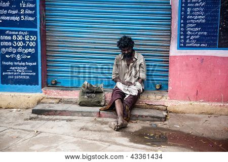 THANJAVUR, INDIA - FEBRUARY 14: Beggar sitting on a street February 14, 2013 in Thanjavur, India. Poverty in India is widespread, with the nation estimated to have a third of the world's poor.