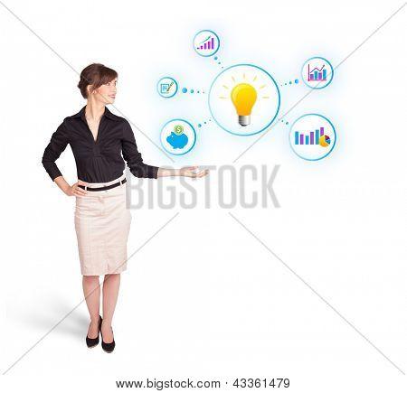 Mujer joven que presenta la bombilla con coloridos gráficos y diagramas aislados en blanco