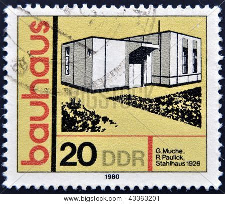 A stamp printed in GDR shows building honoring Bauhaus architectural school Steel building