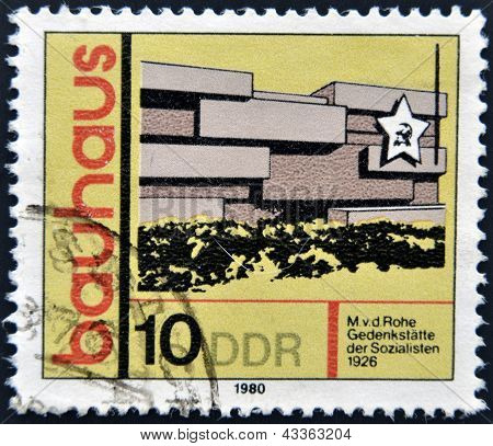 A stamp printed in GDR (East Germany) shows building, honoring Bauhaus architectural school