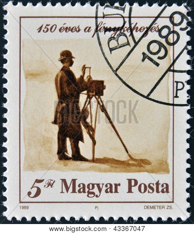 stamp printed in Hungary dedicated to 150 years of photography shows a person shooting the landscape