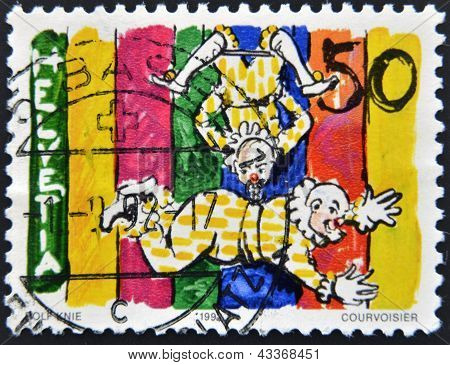 A stamp printed in Switzerland shows a trapeze clown