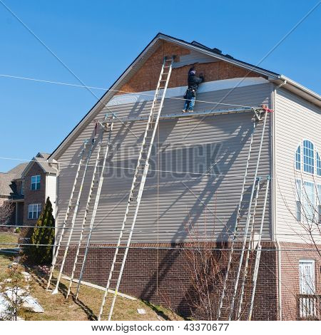 Workers Installing Plastic Siding Panels On Two Story House.