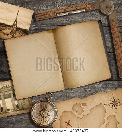 Open diary top view with old treasure map and compass