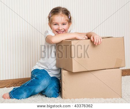 Little girl moving into new house, siting near cardboard box