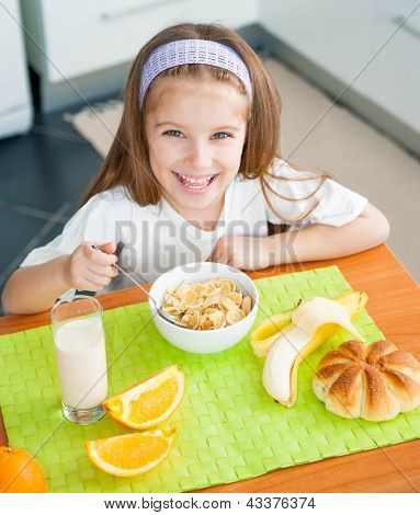 cute little girl eating cereal in the kitchen