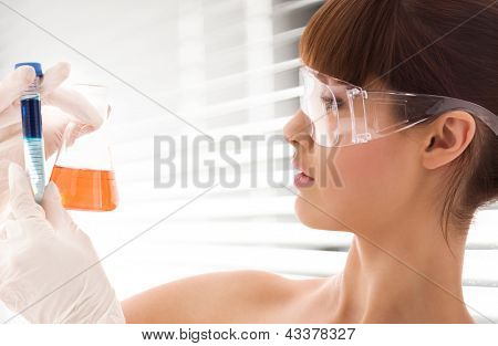 closeup of beautiful lab worker holding up test tubes