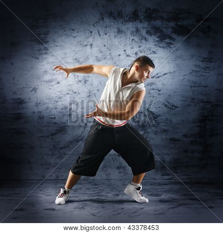 Young and sporty modern dancer over the dramatic background