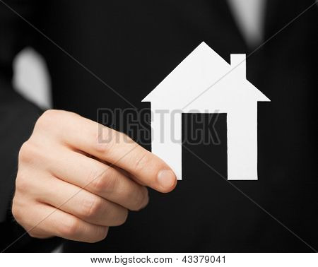 closeup pisture of man in suit holding paper house