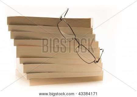 Reading glasses perched on top of a pile of books