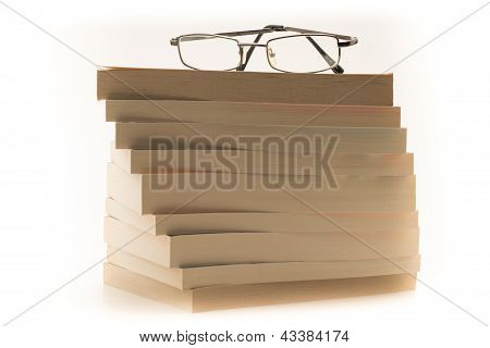 Reading glasses on top of a pile of books