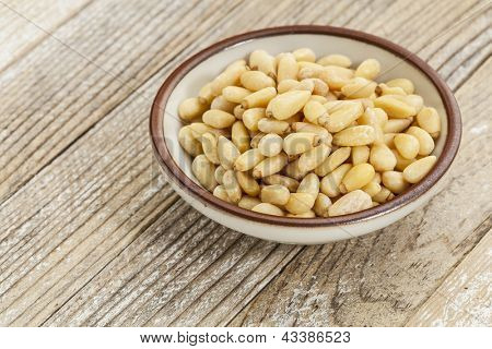 small ceramic bowl of pine nuts against white painted grunge wood surface