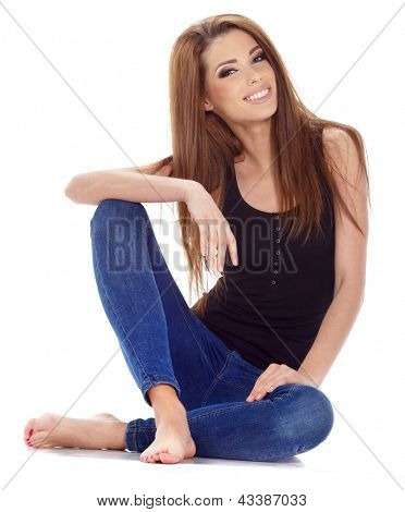Beautiful brunette woman sitting on the floor . Studio shoot.
