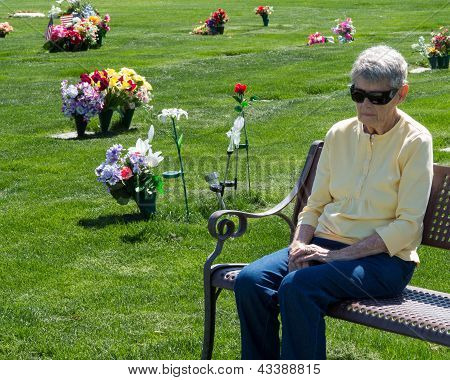 Old woman sitting on cemetery bench